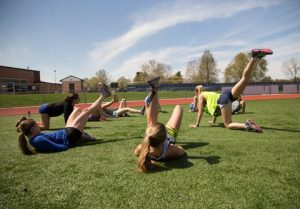 High school running athletes in exercise positions